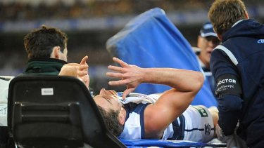 Crunch: Daniel Menzel is carried from the ground.