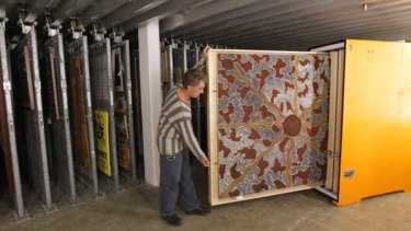 Conservator Mark Henderson packs paintings from the Papunya exhibition, including Honey Ant Hunt by Tim Leura Tjapaltarni.