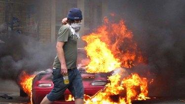 Riots ... a masked man walks past a burning car in Hackney.