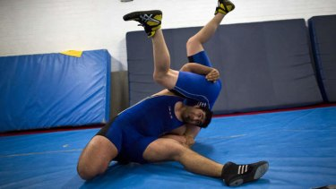 Champion: (Clockwise from top left) Arzhang Janipour grappling an opponent during training.
