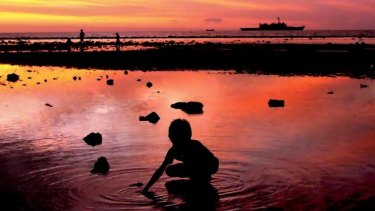 Boundary: A child collects shells as an Australian navy ship patrols along the shore in Dili, East Timor.