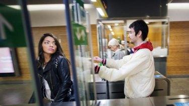 Alex Berthelsen, right, slips through subway station gates in Stockholm.