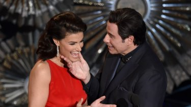 Idina Menzel, left, and John Travolta present the award for best original song at the Oscars at the Dolby Theatre in Los Angeles.