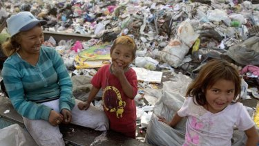 Dirty work: A scavenger with two children takes a break during her labours at the Bordo Poniente dump.