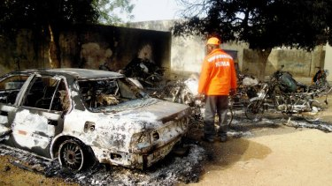 A rescue worker inspects the burnt-out wreckage of cars and motorcycles destroyed by multiple explosions in the northern Nigerian city of Kano.