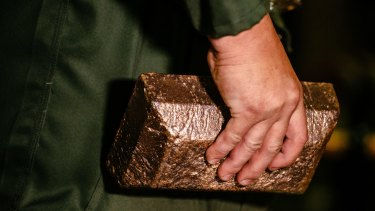 A worker carries a 28 kilogram gold bar.