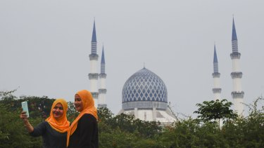Malaysians front of the Sultan Salahuddin Abdul Aziz Shah Mosque, also known as the Blue Mosque, slightly obscured by haze in Shah Alam, Malaysia on Sunday.