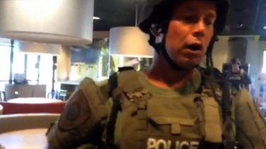 This image taken from video, provided by journalist Wesley Lowery of The Washington Post, shows a police officer confronting Lowery in a fast-food restaurant in Ferguson.