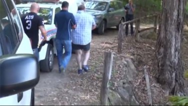 One of the alleged Rebels bikies is arrested by police. Photo: Queensland Police Service.