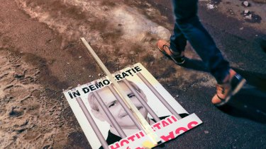 """A broken poster depicting the leader of the ruling Social Democrat party Liviu Dragnea, which reads """"In a democracy, thieves are in jail"""", lies on the pavement in Bucharest, Romania."""