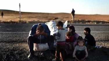 Kurdish refugees sit on the side of the road after fleeing Kobane.