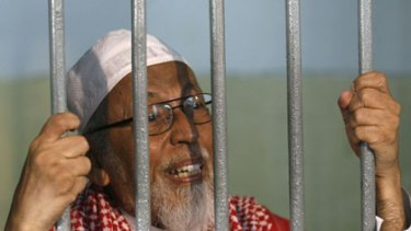 Has pleaded not guilty ... Abu Bakar Bashir talks to journalists from a cell at the court before his hearing.