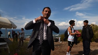 Abdullah al-Salman, from Syria, straightens his tie as he dresses in his best suit moments after arriving by rubber dinghy with about 45 other refugees from Syria, Iraq and Afghanistan at the Greek island of Lesvos  after a three-hour journey from Turkey.