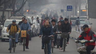People ride on bicycles through haze in Beijing, China, earlier this year.