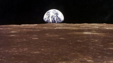 The Earth as seen from the Apollo 11 command module as it orbits the Moon before the landing of the lunar module.