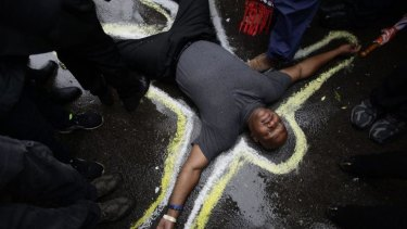Stark message: Pastor Charles Burton has his body outlined with chalk to replicate a crime scene as he and other demonstrators protest the shooting of Michael Brown outside the Ferguson police station.