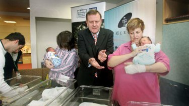 Then treasurer Peter Costello visiting babies born after he introduced the baby bonus scheme.