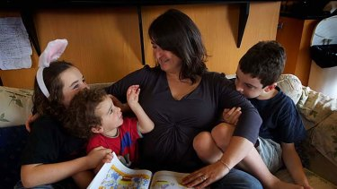 Non-religious Amanda Cox with her sons (from left) Matthew, 10, Charie, 2, and Jamie, 8, reading a Christmas story.