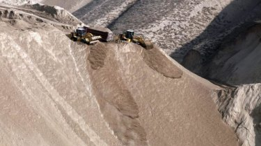 Chinese earth-movers shave off mountaintops in Lanzhou, Gansu province, to make way for cities.