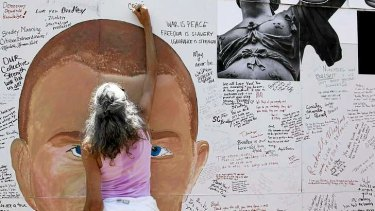 Democracy in action? A supporter signs a mural backing WikiLeaks leaker Private Bradley Manning.