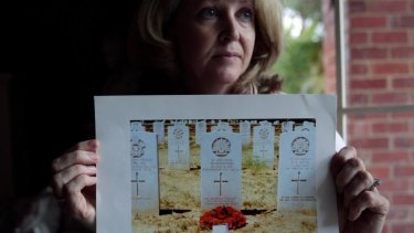 Robyn Burden with a photograph of the grave of her grandfather Walter Ayton.