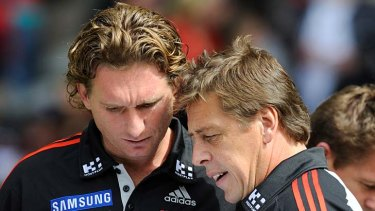 Essendon coach James Hird takes advice from Mark Thompson.