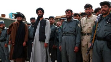 The man who would be king ... Matiullah Khan, centre in grey,  stands with co-workers deciding who may use the road between Kandahar and Tarin Kowt.