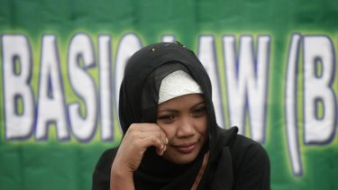 A Filipina Muslim sits in front of a banner during a rally in support of the Bangsamoro Basic Law draft.