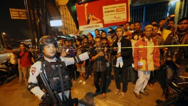 Police officers clear the scene after an explosion near a bus stop in the Kampung Melayu area of Jakarta.