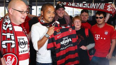 Shinji Ono holds a Western Sydney Wanderers playing shirt as he poses with supporters after his arrival at Sydney International Airport.
