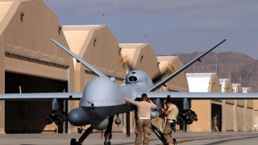US airmen prepare a US Air Force MQ-9 Reaper drone as it leaves on a mission at Kandahar Air Field, in Afghanistan