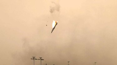 A parachute is ejected from a Libyan jet bomber as it crashes after being hit over Benghazi today as Libya's rebel stronghold came under attack.