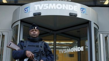 Target of Islamist hackers ... A French police officer stands guard in front of the main entrance of French television network TV5Monde headquarters in Paris on Thursday.