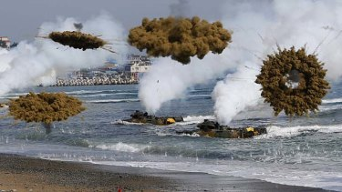 Amphibious assault vehicles of the South Korean Marine Corps throw smoke bombs during a US-South Korea joint landing operation drill in Pohang on Monday.