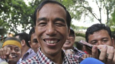 """Joko Widodo, popularly known as """"Jokowi"""", smiles as he is mobbed after a press conference in Jakarta on Wednesday."""