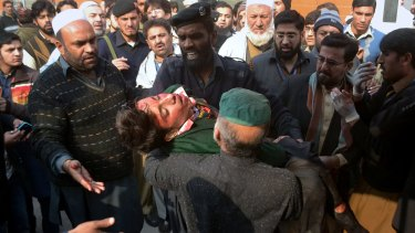 Hospital security guards carry a student injured in the shootout at a school under attack by Taliban in Pakistan.