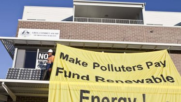 Climate change activists hang banners from, and place solar panels on, federal Climate Change Minister Greg Combet's office.