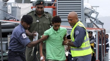 One of the three boys is helped ashore at the Suva naval base yesterday.