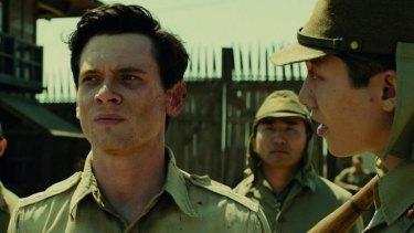Working class hero: Jack O'Connell stars as American prisoner of war Louis Zamperini in the film <i>Unbroken</i>.