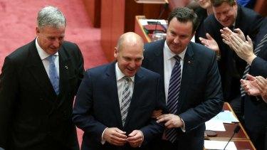 "Senator Richard Colbeck (left) and Senator David Bushby (right) ""drag"" the new President of the Senate, Liberal Senator Stephen Parry to the chair."