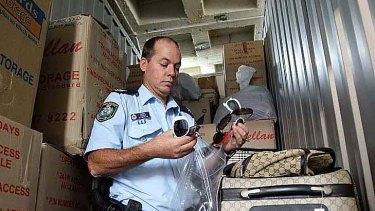 Sergeant Greg Cooper with counterfeit goods seized in raids in Sydney.