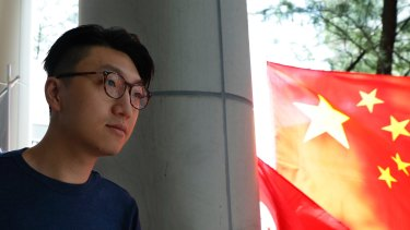Hong Kong localist leader Edward Leung  walks past a Chinese national flag outside a court after he was charged with rioting on August 5.