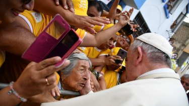 Pope Francis greets a woman after blessing her as he toured around the Plaza de Armas, in Trujillo, Peru on Saturday.