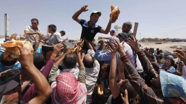Caught in the crush: Syrian refugees gather for food aid after crossing into Iraq.