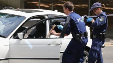 Forensic police remove evidence from the car on Saturday.