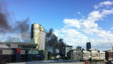 Smoke billows over Docklands, as seen from LaTrobe Street.