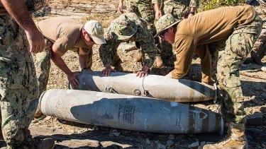Members of the US Navy place bombs recovered from the Great Barrier Reef at a disposal site near Shoalwater Bay Training Area.