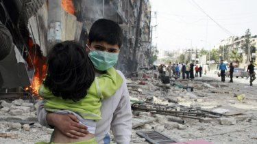 A boy carries a girl after what activists said was an air strike by forces loyal to Syrian President Bashar Al-Assad in Aleppo's Bustan al-Qasr on April 18.