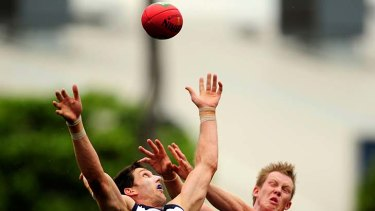 Eyes on the ball: Geelong's Harry Taylor keeps the Sherrin in sight against Richmond's Jack Riewoldt.