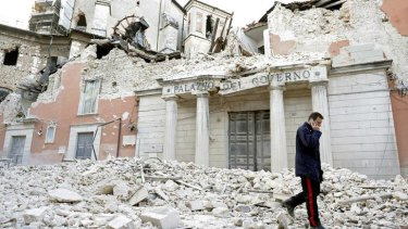 Aftermath .... a man walks past buildings destroyed in the earthquake.